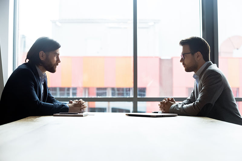 Two Men sitting across from each other at a table.